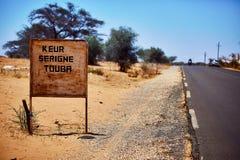 Указатель к touba в Сенегале, ландшафту пустыни предпосылки расплывчатому Стоковое Изображение