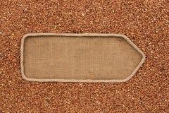 Указатель сделанный от веревочки при гречиха зерен лежа на дерюге Стоковое Изображение RF