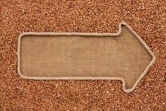 Указатель сделанный от веревочки при гречиха зерна лежа на дерюге Стоковое Изображение RF