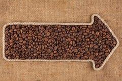 Указатель сделанный от веревочки при кофейные зерна лежа на дерюге Стоковое Фото