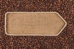Указатель сделанный от веревочки при кофейные зерна лежа на дерюге Стоковое фото RF
