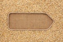 Указатель сделанный от веревочки при овсы зерен лежа на дерюге Стоковые Фото