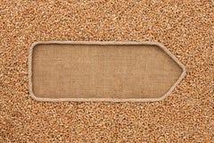 Указатель сделанный от веревочки при пшеница зерна лежа на дерюге Стоковая Фотография RF