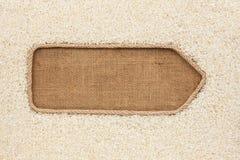 Указатель сделанный от веревочки при рис зерен лежа на дерюге Стоковые Фото