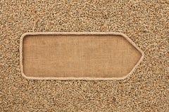 Указатель сделанный от веревочки при рожь зерен лежа на дерюге Стоковая Фотография