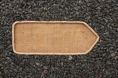 Указатель сделанный от веревочки при семена подсолнуха лежа на дерюге Стоковое Изображение