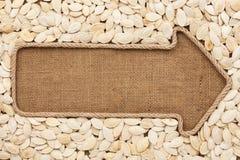 Указатель сделанный от веревочки при семена тыквы лежа на дерюге Стоковое Изображение RF
