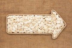 Указатель сделанный от веревочки при семена тыквы лежа на дерюге Стоковые Фото