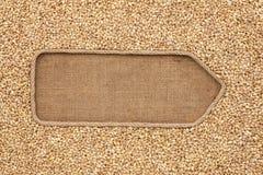 Указатель сделанный от веревочки при ячмень жемчуга зерен лежа на дерюге Стоковое Изображение