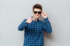 Указывать солнечных очков счастливого человека нося стоковая фотография