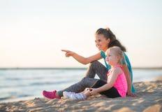 Указывающ мать с дочерью в разминке зацепите сидеть на пляже стоковое фото rf
