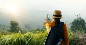 Укладывайте рюкзак использующ smartphone принимая изображению красивый ландшафт на горном пике пока исследовать, trekking в тропи стоковые изображения