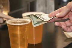 Укомплектовывает личным составом руку оплачивая для 2 пластиковых чашек пива с двадцатидоллоровой банкнотой USD стоковые фотографии rf