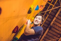 Укомплектуйте личным составом альпиниста на искусственной взбираясь стене в bouldering спортзале Стоковое фото RF
