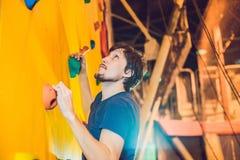 Укомплектуйте личным составом альпиниста на искусственной взбираясь стене в bouldering спортзале Стоковое Изображение