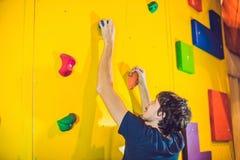 Укомплектуйте личным составом альпиниста на искусственной взбираясь стене в bouldering спортзале Стоковые Изображения RF