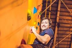 Укомплектуйте личным составом альпиниста на искусственной взбираясь стене в bouldering спортзале Стоковое Фото