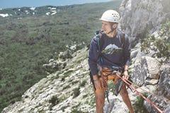 Укомплектуйте личным составом альпиниста утеса на верхней части скалы и belays партнер Стоковые Фото
