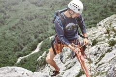 Укомплектуйте личным составом альпиниста утеса на верхней части скалы и belays партнер Стоковое Изображение