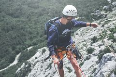Укомплектуйте личным составом альпиниста утеса на верхней части скалы и belays партнер Стоковое Изображение RF