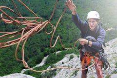 Укомплектуйте личным составом альпиниста утеса на верхней части скалы и ходов веревочка к партнеру Стоковые Фотографии RF