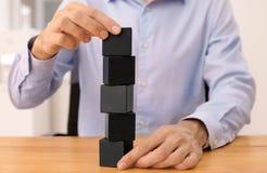 Укомплектуйте личным составом башню здания от деревянных блоков на таблице Стоковые Изображения RF