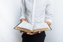 Укомплектуйте личным составом библию чтения, белую предпосылку, книгу в конце-вверх руки Стоковые Фотографии RF