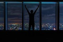 Укомплектуйте личным составом веселить пока смотрящ вне большие окна высокие над разваливаясь городом Стоковое фото RF