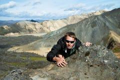 Укомплектуйте личным составом взбираться к верхней части горы Стоковое фото RF
