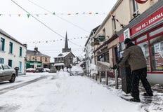 Укомплектуйте личным составом выскабливать снег на фронте паба Стоковое Изображение RF