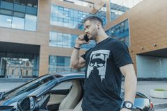 Укомплектуйте личным составом выходить черного автомобиля и говорить мобильным телефоном Взгляд со стороны стоковое фото