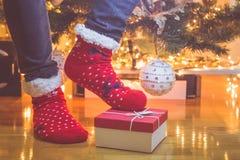 Укомплектуйте личным составом в носках и подарочной коробке рождества красных цветов на поле против украшенной предпосылки рождес стоковые изображения
