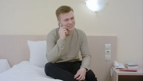 Укомплектуйте личным составом говорить и смеяться над на его smartphone усаженном на кровать Стоковая Фотография