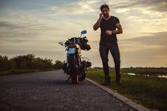 Укомплектуйте личным составом говорить на телефоне его велосипедом стоковая фотография rf