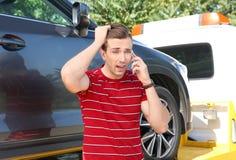 Укомплектуйте личным составом говорить на телефоне около сломленных автомобиля и эвакуатора стоковое изображение