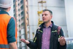 Укомплектуйте личным составом говорить о проблемах на строительном проекте проектировать стоковые изображения rf