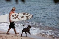 Укомплектуйте личным составом гулять на пляж с его собакой Стоковые Фото