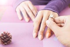 Укомплектуйте личным составом давать обручальное кольцо к его подруге, обручальное кольцо, Diam Стоковая Фотография