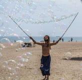 Укомплектуйте личным составом делать пузыри мыла на пляже Barceloneta в Барселоне, Испании стоковая фотография