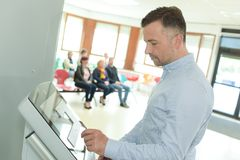 Укомплектуйте личным составом делать регистрацию на столе самопомощи в авиапорте Стоковые Изображения RF