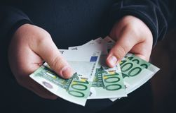 Укомплектуйте личным составом держать 100 банкнот евро в его руках подсчитывать его деньги человека Стоковые Фото