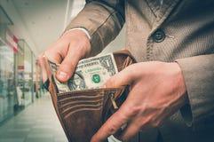 Укомплектуйте личным составом держать кожаный бумажник с только одним долларом внутрь стоковое фото rf