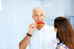 Укомплектуйте личным составом держать красный пеец рядом с его стороной Стоковые Изображения