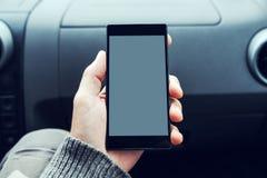 Укомплектуйте личным составом держать мобильный телефон с пустым экраном в автомобиле Стоковое Изображение