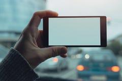 Укомплектуйте личным составом держать мобильный телефон с пустым экраном в автомобиле Стоковые Изображения RF