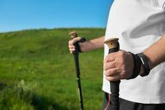 Укомплектуйте личным составом держать отслеживать ручки на предпосылке зеленой травы Стоковое фото RF