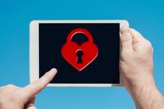 Укомплектуйте личным составом держать прибор таблетки показывая значок замка сердца Стоковые Фотографии RF