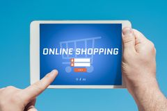 Укомплектуйте личным составом держать прибор таблетки посещая онлайн вебсайт покупок стоковое фото rf