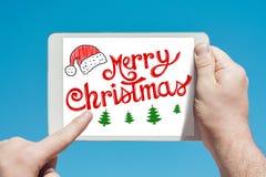 Укомплектуйте личным составом держать прибор таблетки с ` ` текста с Рождеством Христовым стоковые изображения rf