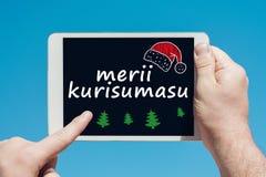 Укомплектуйте личным составом держать прибор таблетки с текстом в японском ` Merii Kurisumasu ` с Рождеством Христовым стоковое фото